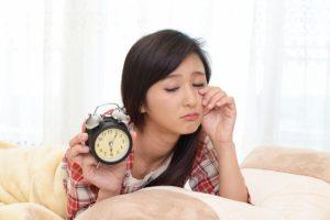 目覚まし時計を手にする女性